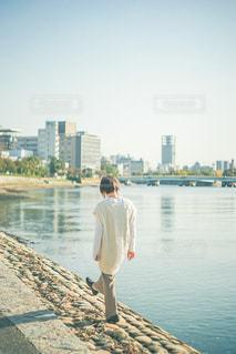 水の体の隣に立っている男の写真・画像素材[3240669]