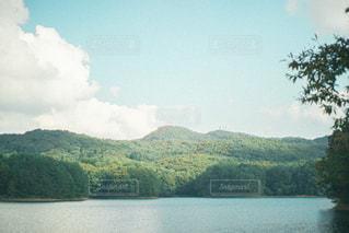 背景に山のある水の体の写真・画像素材[3240674]
