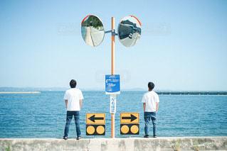 水の体の前に立っている男の写真・画像素材[3240681]