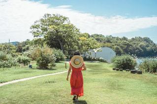 赤いフリスビーの隣に立っている人の写真・画像素材[3240687]