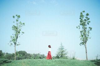 木の隣に立っている男の写真・画像素材[3240695]