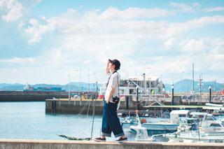 水の体の隣に立っている男の写真・画像素材[3240720]