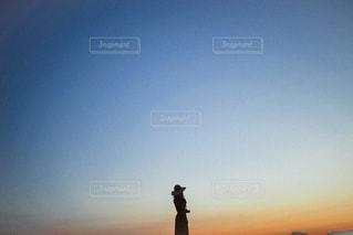 夕日の前に立っている男の写真・画像素材[3339324]