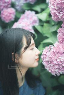 植物の上のピンクの花の女性のクローズアップの写真・画像素材[3375174]