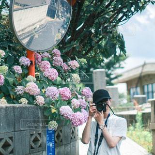 携帯電話で話している建物の前に立っている人の写真・画像素材[3375198]