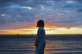 水の体の隣に立っている男の写真・画像素材[3397413]