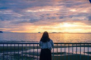 水の体の隣の桟橋の前に立っている男の写真・画像素材[3397417]
