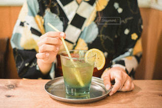 コーヒーを飲みながらテーブルに座っている人の写真・画像素材[3488759]