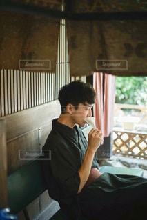 携帯電話で話している窓の前に立っている人の写真・画像素材[3528069]