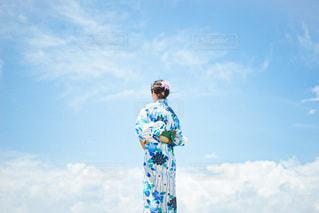 曇った青空の前に立っている人々のグループの写真・画像素材[3528071]