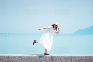 水の体の隣に立っている男の写真・画像素材[3552296]
