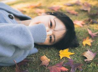 草の中に横たわる小さな女の子の写真・画像素材[3716496]