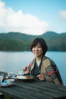 水の体の前のテーブルに座っている人の写真・画像素材[3756278]