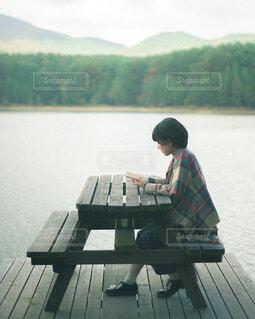 水の体の隣のベンチに座っている人の写真・画像素材[3756277]