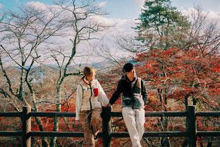 フェンスの前に立っている男女の写真・画像素材[3944749]