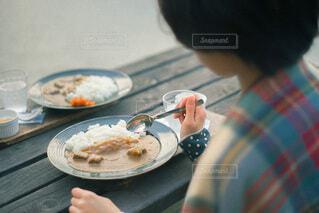 食べ物の皿をテーブルの上に持っている人の写真・画像素材[4199579]