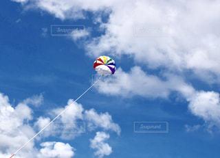 青空に広がる白い雲と虹色のパラグライダーの写真・画像素材[2414318]