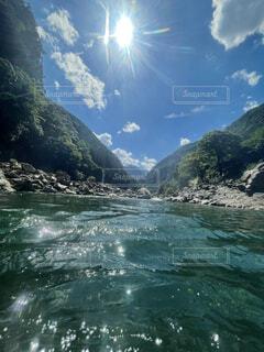 背景に山のある水の体の写真・画像素材[4718470]