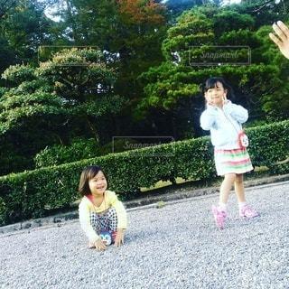 木の隣に立っている小さな女の子の写真・画像素材[2346938]