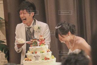ケーキを持ってテーブルに座っている人々のグループの写真・画像素材[2354286]