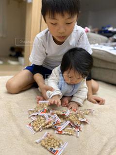 テーブルの上に座っている小さな子供の写真・画像素材[2924671]