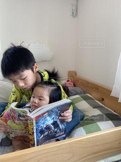 ベッドに座っている小さな子供の写真・画像素材[3159218]