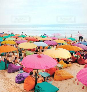 カラフルな傘を持つビーチの人々のグループの写真・画像素材[2348369]