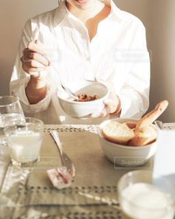 コーヒーを飲みながらテーブルに座っている男の写真・画像素材[2497768]