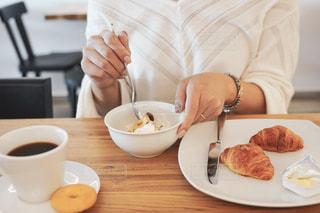 皿の食べ物とコーヒー1杯の写真・画像素材[2497775]