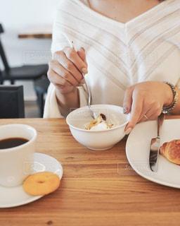 コーヒーを飲みながらテーブルに座っている人の写真・画像素材[2497777]