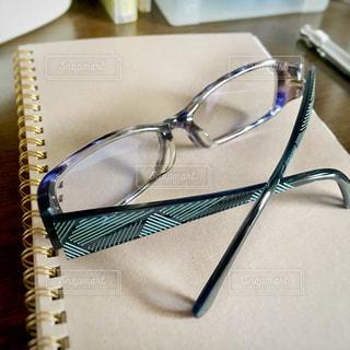 机の上のメガネと手帳の写真・画像素材[2761364]