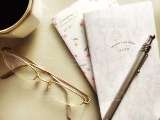 テーブルの上のコーヒーとメガネと手帳の写真・画像素材[2763298]