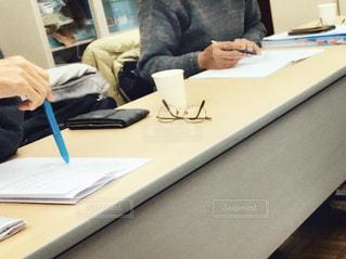 男性,コーヒー,手,スマホ,テーブル,ペン,机,人物,人,書類,紙コップ,ビジネス,紙,コンピューター,会議,メガネ,会議室,電話機,会議中,資料,説明,データ,書き込み,ノート パソコン,ビジネスシーン,決算,検討,収支,月次資料,議題