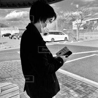 男性,1人,ファッション,風景,空,屋外,黒,モノクロ,車,道路,スマホ,人物,道,人,コーディネート,コーデ,通り,マスク,車両,ブラック,スマホいじり,ピーコート,黒コーデ,黒と白