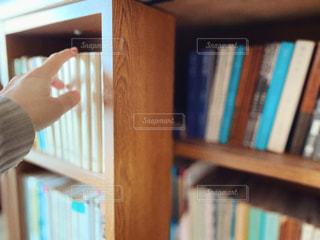 本棚で本を選んでいる人の写真・画像素材[2899734]