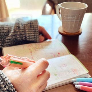コーヒーを飲みながらテーブルに座っている人の写真・画像素材[2999553]