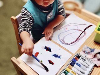 テーブルの上に座っている小さな子供の写真・画像素材[3222735]
