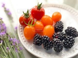 皿の上に乗ったとれたてミニトマトとブラックベリーの写真・画像素材[3672435]