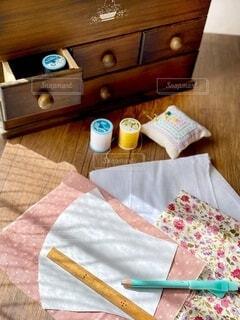 木製のテーブルの上の裁縫箱と布の写真・画像素材[3773754]