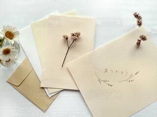 ドライフラワーをつけた封筒と手書きメッセージの写真・画像素材[3877694]