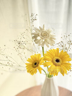 テーブルの上の黄色い花の花瓶の写真・画像素材[4295769]