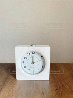木製のテーブルの上に座っている時計の写真・画像素材[2904490]