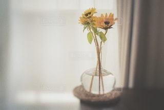 テーブルの上に座る花で満たされた花瓶の写真・画像素材[3499571]