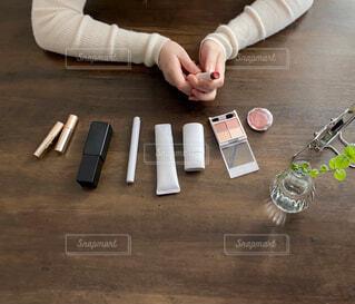 木製のテーブルの上に座っている人の写真・画像素材[4296353]