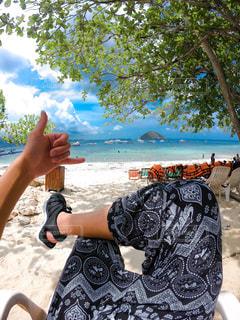 水域の近くの浜辺に座っている男性の写真・画像素材[2377954]