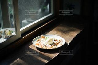 窓の前の木製のテーブルの上に座っているピザの写真・画像素材[2875746]