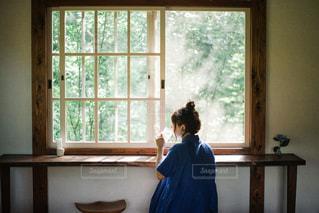 窓の前に立っている人の写真・画像素材[2875748]