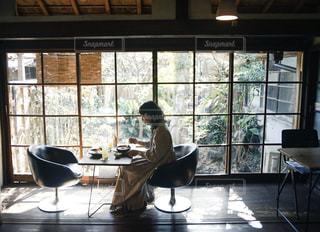 窓の前のダイニングルームのテーブルの写真・画像素材[2875756]