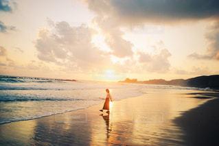 水域の隣のビーチを横切って歩く男の写真・画像素材[2877849]