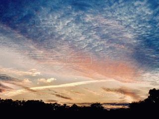 飛行機雲とオレンジ色のうろこ雲の写真・画像素材[2420416]